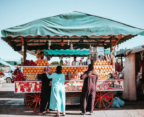 Photo de femmes marocaines voilées achetant du jus de fruit à une calèche d'orange à Marrakech