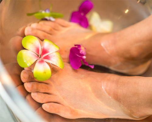 massage pieds avec une fleur verte
