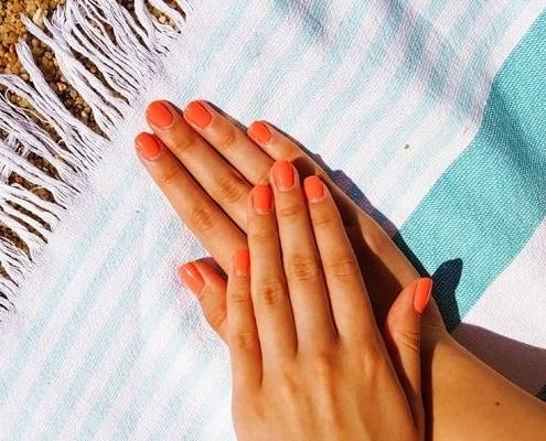 mains sur une serviette de plage avec des ongles oranges après une pédicure
