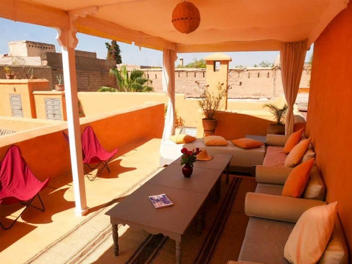 Pergola blanche et orange sur une terrasse ocre dans un riad à Marrakech Maroc
