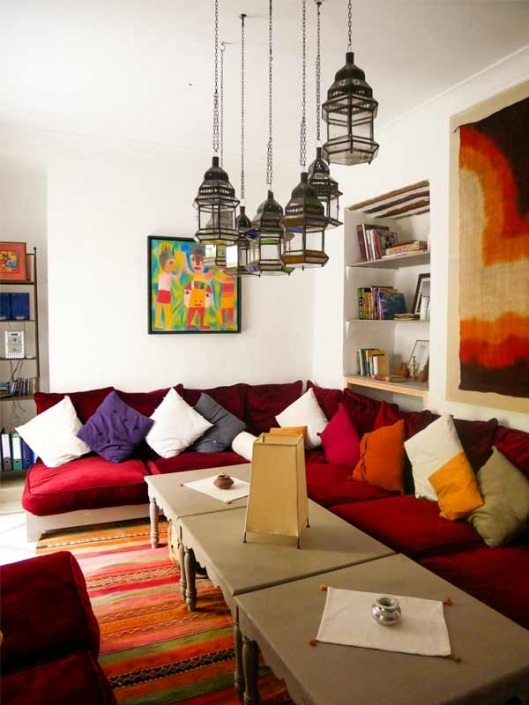 Photo d'un salon rouge avec des lanternes marocaines dans un riad à Marrakech