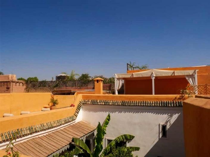Photo d'une terrasse aux murs ocre avec des bananiers dans un riad à Marrakech Maroc
