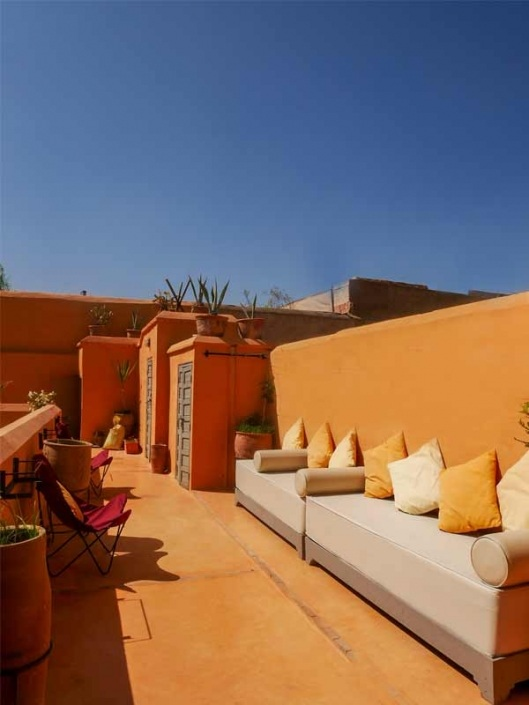 Photo de canapés blanc et orange sur une terrasse aux murs ocre dans un riad à Marrakech